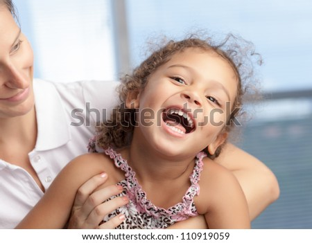 Playful little girl laughing in her mother�s hands - stock photo