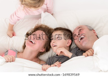 Playful little girl with her family in bed clambering over the top of the pillow making them laugh with amusement and pleasure as her brother and parents snuggle together under the bedclothes - stock photo