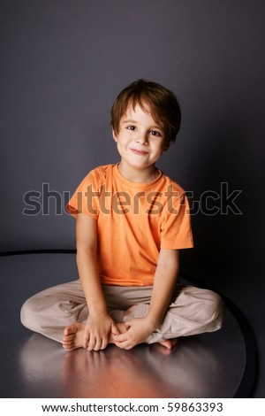 Playful little smiling boy sitting in a lotus pose, studio shot - stock photo