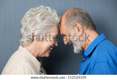 Playful loving senior couple standing facing each other with their foreheads touching smiling happily at each other - stock photo