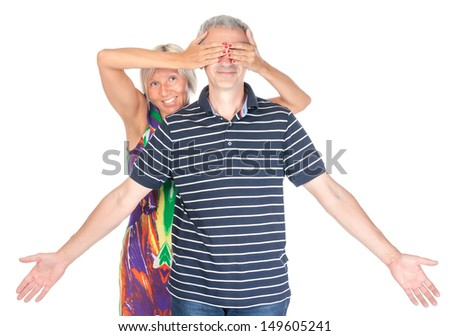 Playful middle-aged couple having fun with the woman holding her hands over the man eyes as he stands with outstretched arms isolated on white - stock photo