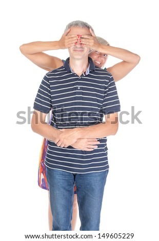 Playful middle-aged couple having fun with the woman holding her hands over the man eyes, isolated on white - stock photo