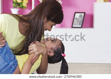 Playful mother and daughter at home - stock photo
