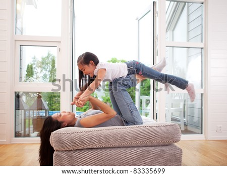 Playful mother giving daughter an airplane ride with arms and feet - stock photo