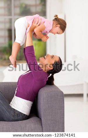 playful mother playing with little daughter at home