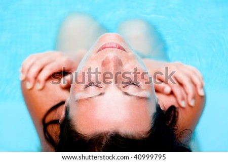Playful pool vacations holiday woman relaxing embracing in water