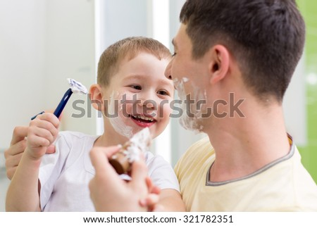 playful preschooler boy attempting to shave his dad - stock photo