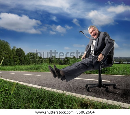 playful senior businessman running on a country road with armchair - stock photo