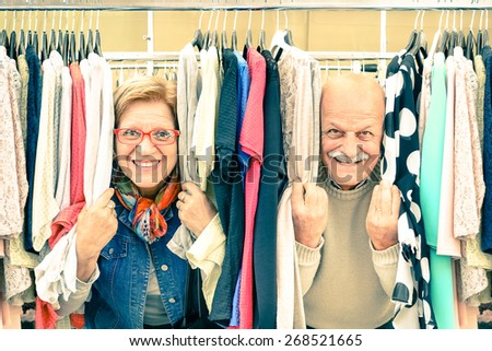 Playful senior couple at weakly flea market - Concept of active elderly with mature man and woman having fun and shopping in the old town - Happy retirement moments on a warm vintage nostalgic look   - stock photo