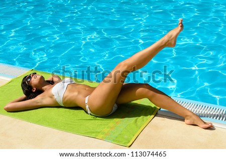 Playful sexy tanned young brunette girl in bikini and sunglasses at poolside sunbathing and relaxing. Caucasian attractive brunette model near the blue water. - stock photo