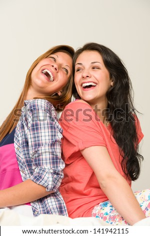 Playful sisters sitting back-to-back and laughing - stock photo