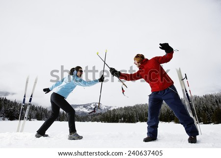 Playful Skiers Fighting with Ski Poles - stock photo