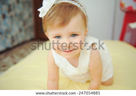playful smiling baby on bed - stock photo