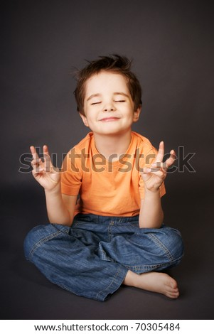 Playful smiling little boy sitting in meditation pose, studio shot - stock photo