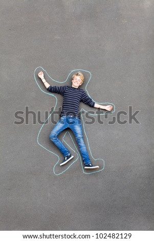 playful teen boy lying on ground with lines drawn around him - stock photo