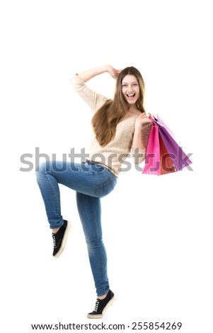Playful teenage girl laughing, jumping, dancing with delight, holding pile of shopping bags. Sale, discount, fashion, profitable offer concepts - stock photo