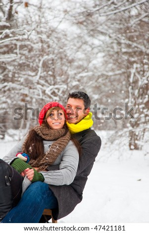 Playful winter couple sledding on sled in park - stock photo