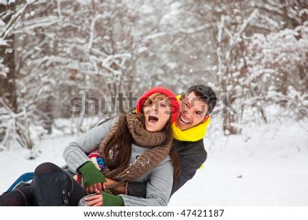 Playful winter couple sledding on sled in park - stock photo