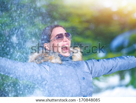 Playful woman having fun on winter park, throwing snow, enjoying wintertime nature, active lifestyle, happiness concept  - stock photo