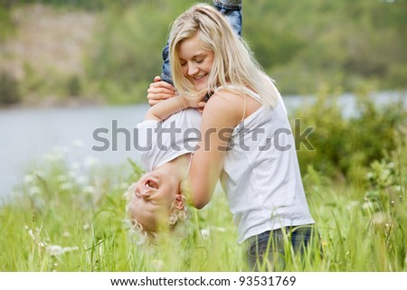 Playful woman in park playing with her laughing son - stock photo