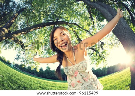 Playful woman in spring having fun in park smiling happy playing joyful. Beautiful young multicultural woman outside on sunny day. - stock photo