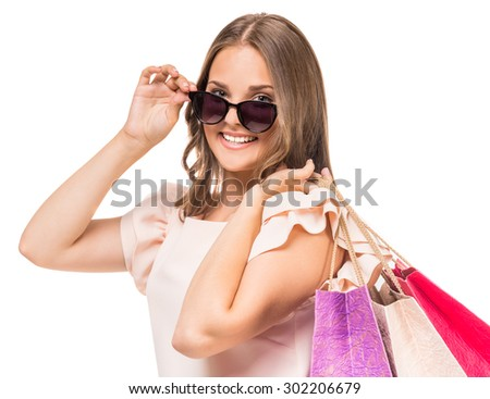 Playful woman in sunglasses holding colored shopping bags on white background. - stock photo
