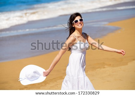 Playful woman on beach summer vacation dancing and having fun. Joyful girl on relaxing summertime walk. - stock photo