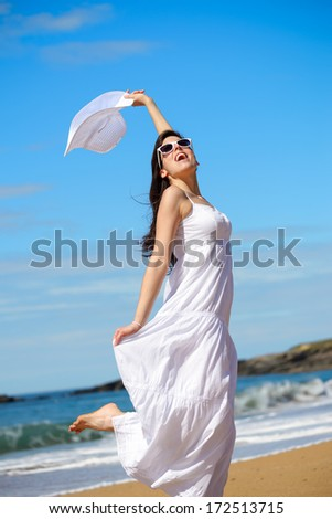 Playful woman on beach summer vacation dancing and playing around. Happy girl enjoying freedom and summertime lifestyle. Asturias, Spain. - stock photo