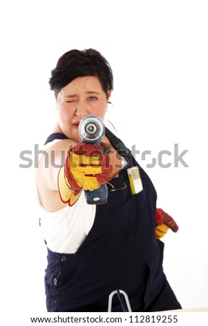 Playful woman taking aim with power drill Playful woman in dungarees and apron taking aim with a handheld electric power drill as she has fun during a DIY project - stock photo