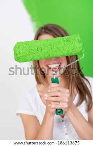 Playful woman with a big grin hiding behind a paint roller full of green paint as she redecorates her house - stock photo