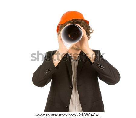 Playful young architect in a hardhat standing spying on the camera using a rolled up blueprint as a telescope, on white - stock photo