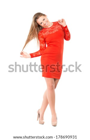 Playful young blonde wearing short red dress. Isolated on white
