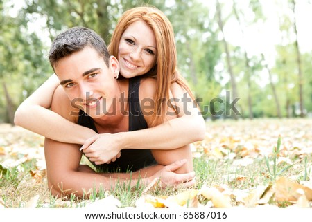 playful young couple in autumn park, smiling and looking at camera