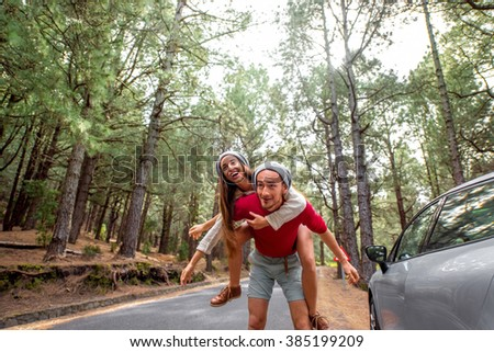 Playful young couple in sweaters and hats having a piggyback ride near the car on the pine forest roadside. Wide angle image with copy space - stock photo