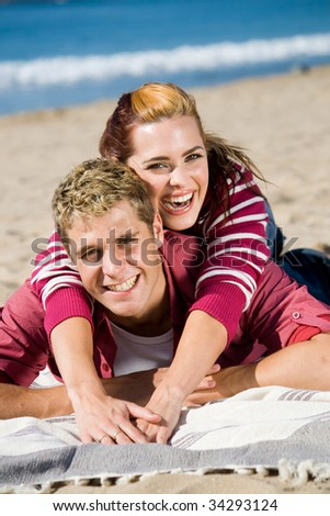 playful young couple on beach