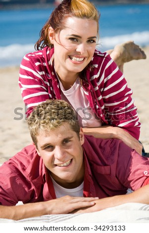 playful young couple on beach having fun