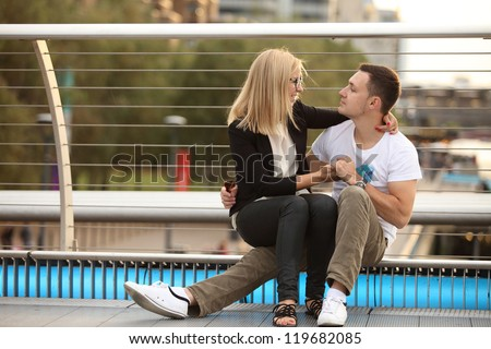 playful young couple sitting on Millennium bridge - stock photo
