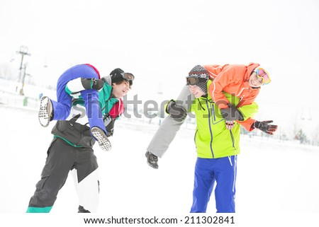 Playful young couples enjoying in snow - stock photo