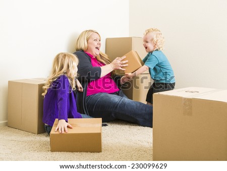Playful Young Family In Empty Room Playing With Moving Boxes.