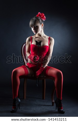 Playful young woman in sexy red lingerie sitting in chair - stock photo