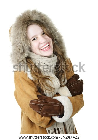 Playful young woman in winter coat on white background - stock photo