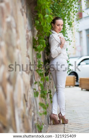 Playful young woman wearing white pants and jacket posing near the wall - stock photo