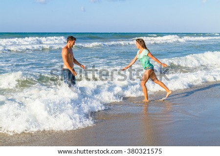 Playfull young couple in bikini and shorts at the beach.