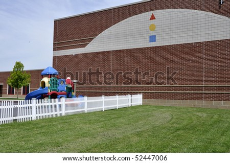 Playground and a white fence by a modern red brick school building.  There is a bright green lawn by the fence. - stock photo