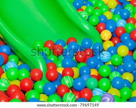 Playground slide and plastic balls - stock photo