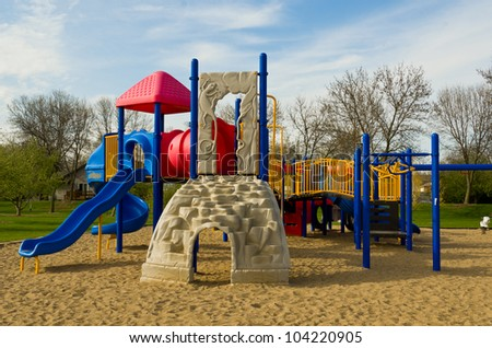 Playground with Multiple Slides in the Late Afternoon - stock photo