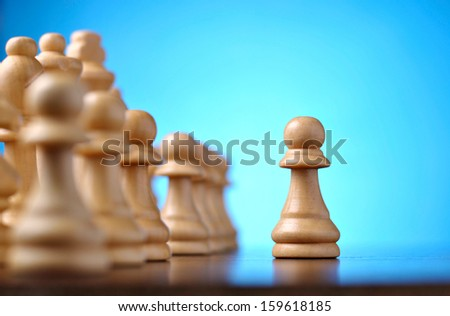 Playing a game of chess with a low angle view of vintage wooden chess pieces on a reflective surface with focus to a single pawn in the foreground and shallow dof - stock photo