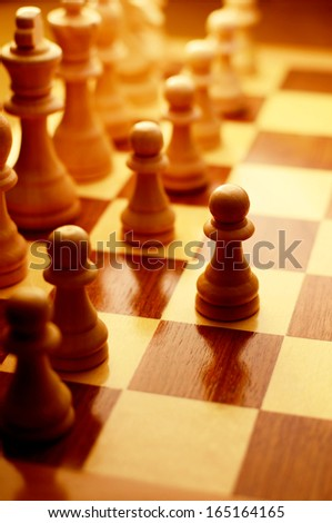 Playing a game of chess with chess pieces lined up on a chessboard with focus to a single pawn that has been advanced to the next row, high angle view - stock photo