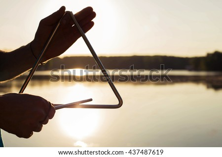 Playing a musical instrument triangle on background sky at sunset - stock photo