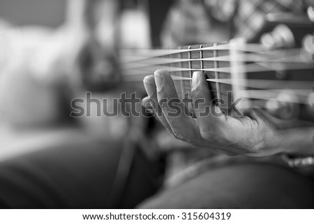 playing acoustic guitar, barre chord,selective focus,black and white tone. - stock photo